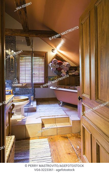 Main bathroom with toilet and clawfoot bathtub on raised ceramic tile platform on the upper floor inside an old circa 1850 Canadiana cottage style home