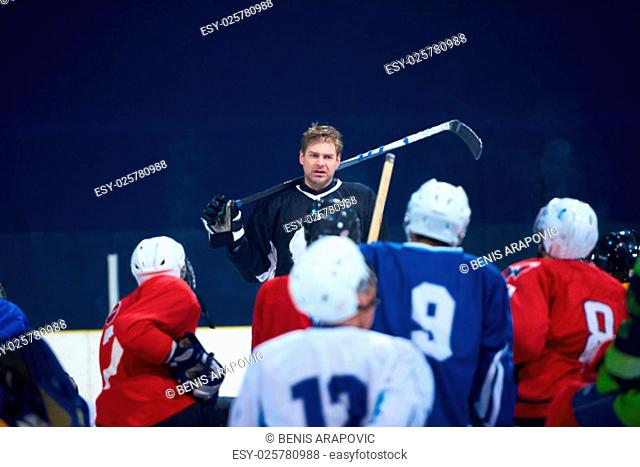 ice hockey players team group meeting with trainer in sport arena indoors