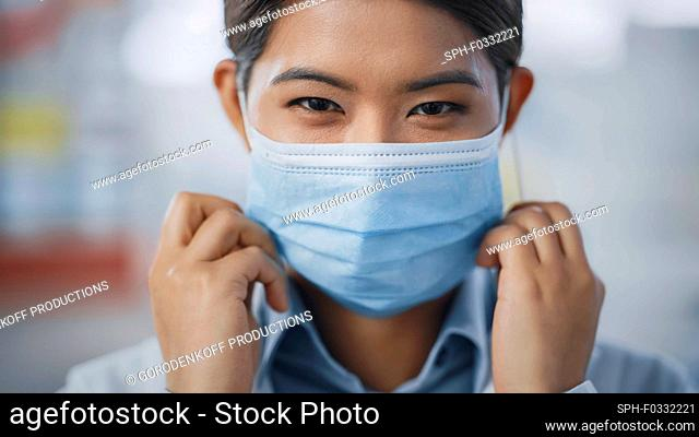 Healthcare professional putting on a face mask