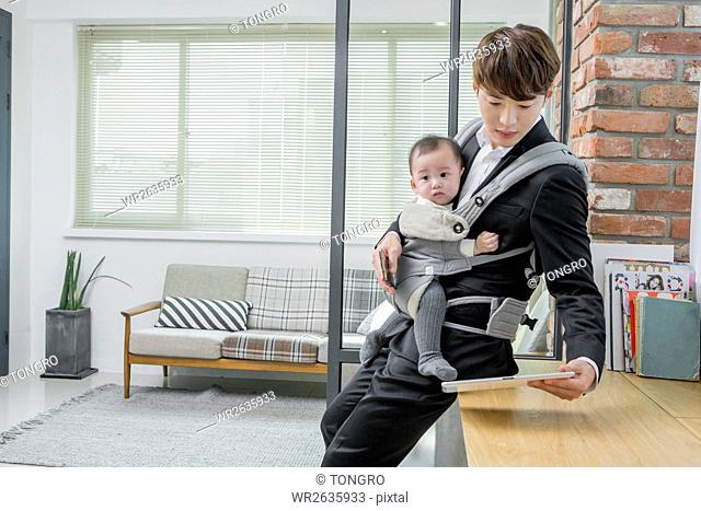Busy businessman working taking care of his baby
