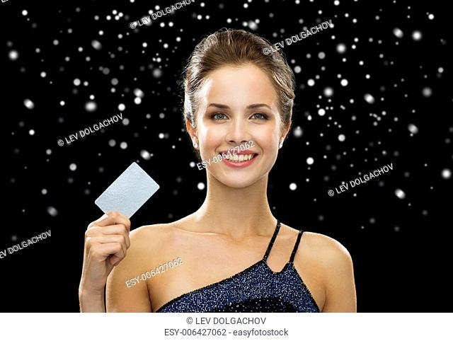 shopping, money, winter holidays, christmas and people concept - smiling woman in evening dress holding credit card over black snowy background