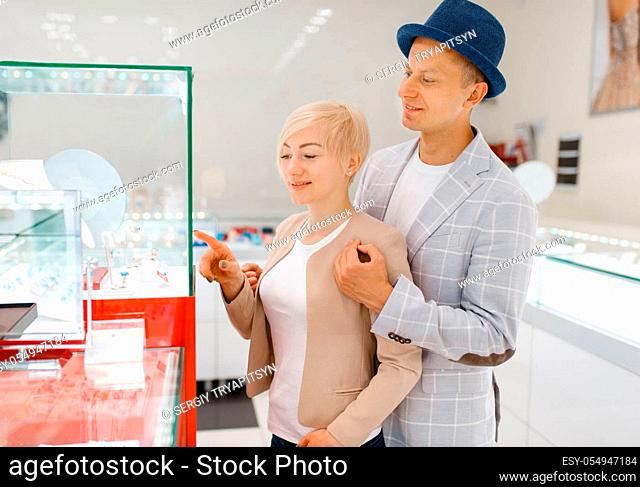 Male and female consumers looking on jewels in jewelry store. Man and woman choosing wedding rings. Future bride and groom in jewellery shop