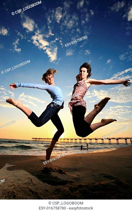Happy girls jumping at the beach at sunset