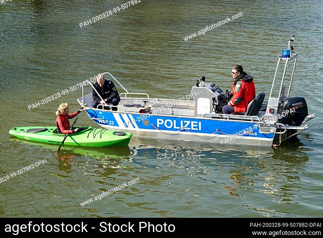 28 March 2020, Saxony, Leipzig: Policemen of the water police control a paddler in the magpie tidal bed. To contain the spread of the coronavirus