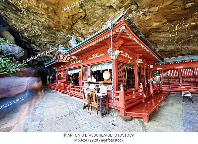 A japanese tourist walking past the main shrine set in the cave of Udo-Jingu shinto temple. Nichinan City. Miyazaki Prefecture. Japan