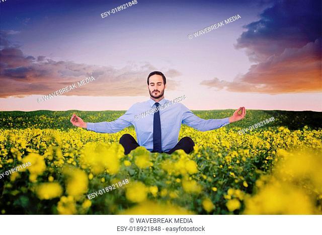 Composite image of businessman in suit sitting in lotus pose