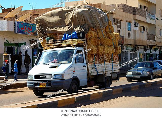 Schwerbeladener Kleintransporter transportiert Strohballen in den Strassen von Germa, LIbyen / Heavily loaded pick-up transporting straw in the streets of Germa