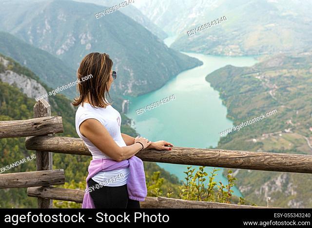 Woman hiker at mountain viewpoint enjoying the view of a lake and canyon