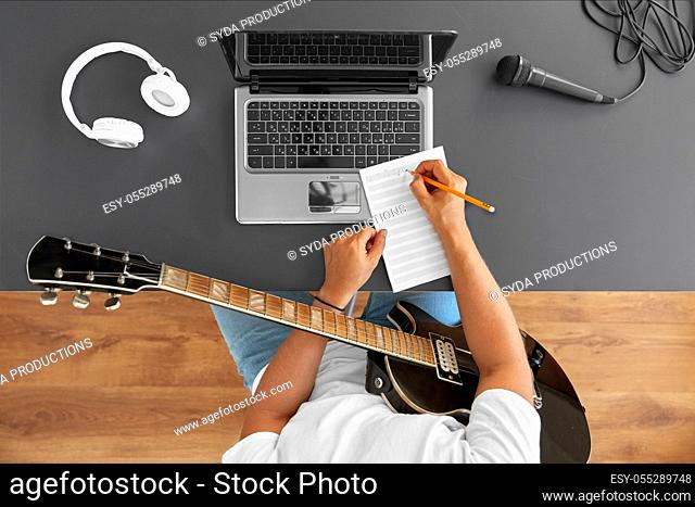 man with guitar writing to music book at table
