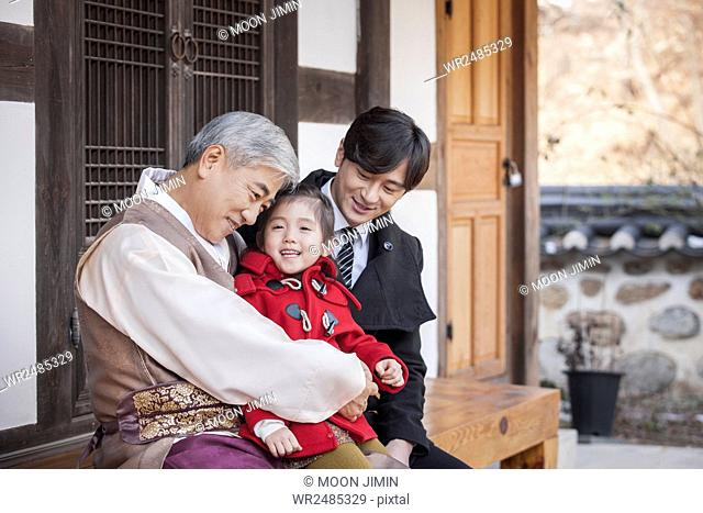 Smiling old man hugging his granddaughter and smiling man with them