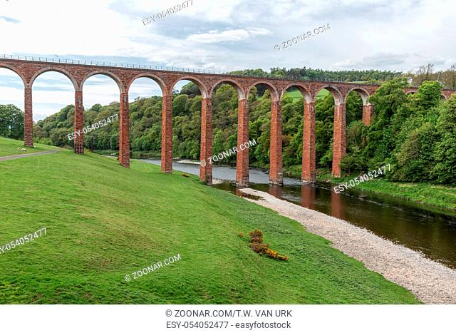 Leaderfoot railway viaduct over the river Tweed near Melrose in the Scottish Borders with grazing sheep