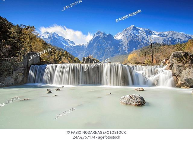 Waterfall on foreground and Jade Dragon Snow Mountain on background - Yunnan, China