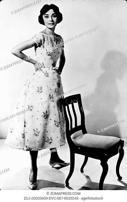 1957, Film Title: LOVE IN THE AFTERNOON, Director: BILLY WILDER, Studio: AA, Pictured: 1957, AUDREY HEPBURN, PORTRAIT, HOMEY, CHAIR, DRESS, FLORAL, LEGS APART