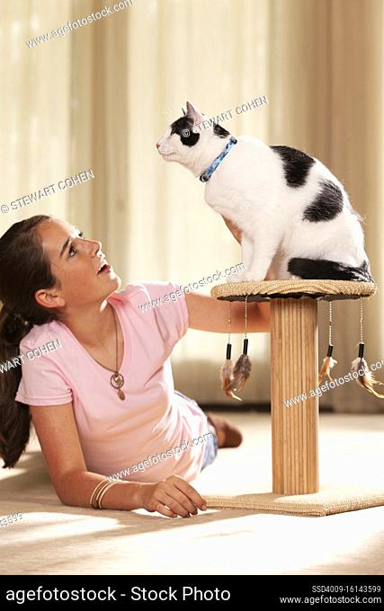 Teenaged caucasian girl lying on rug in living room petting her cat, cat sitting on top of scratching post looking off camera
