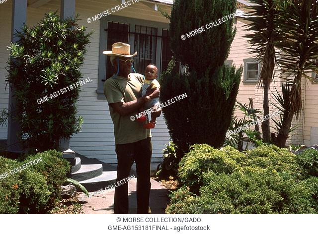Portrait of a smiling African American man holding an infant African American boy, outside a home in Los Angeles, California, July, 1975