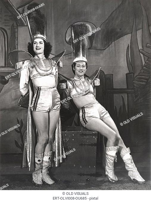 Two performers dressed in magician assistant costumes