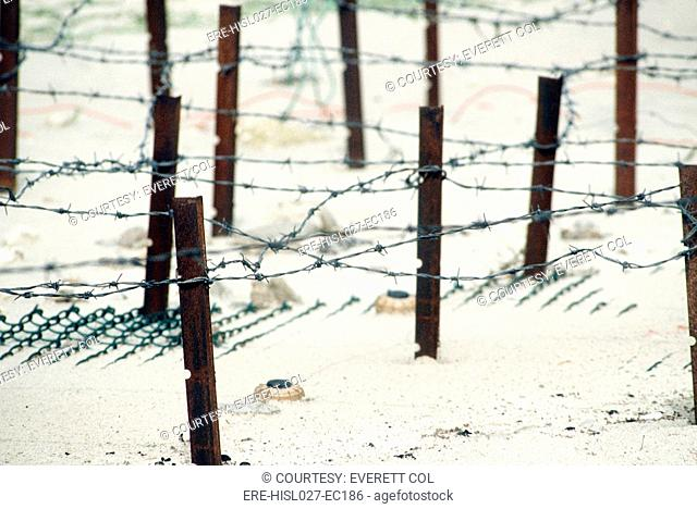 Iraqi anti-personnel mines and barbed wire fences line a beach prior to being cleared in the aftermath of Operation Desert Storm. 1991