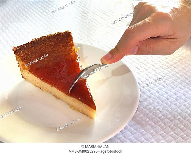 Man's hand having a piece of cheese cake