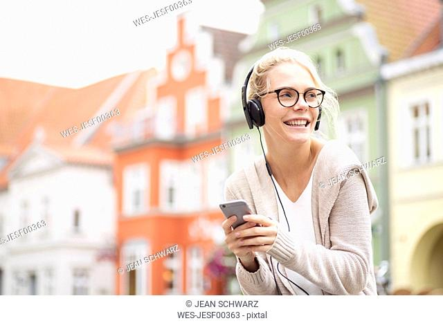 Portrait of blond woman using smartphone and headphones