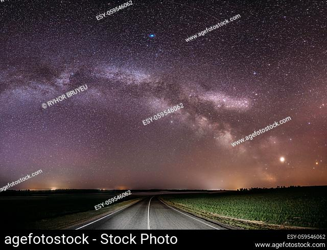 Magenta Night Starry Sky Above Country Asphalt Road In Countryside And Green Field. Night View Of Natural Glowing Stars And Milky Way Galaxy