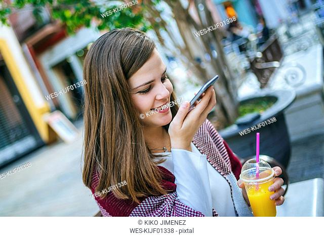 Young woman in Sevilla drinking fruit juice and sing smart phone