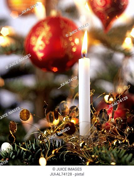 Detail toned view of Christmas ornaments with a burning candle in foreground