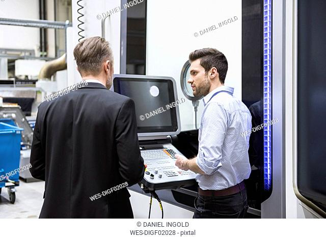 Two men talking at control in modern factory