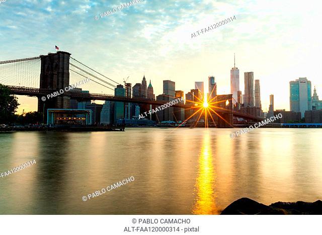 Manhattan skyline and Brooklyn Bridge at sunset