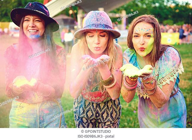 Three young women blowing coloured chalk powder at festival