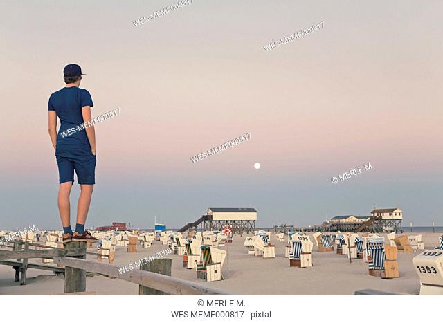 Germany, St Peter-Ording, young man standing on wooden fence looking at the beach