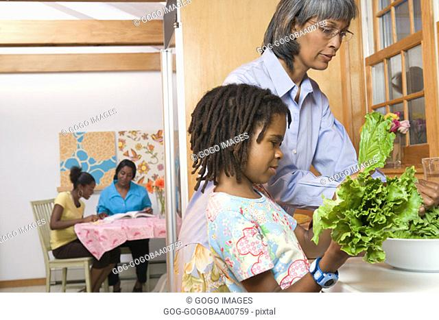 Young African girl cooking with her grandmother
