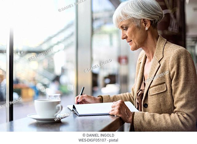 Senior businesswoman taking notes in a cafe