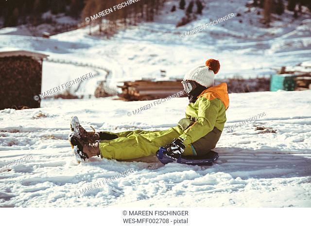 Italy, Val Venosta, Slingia, boy sleighing down a snowy hill