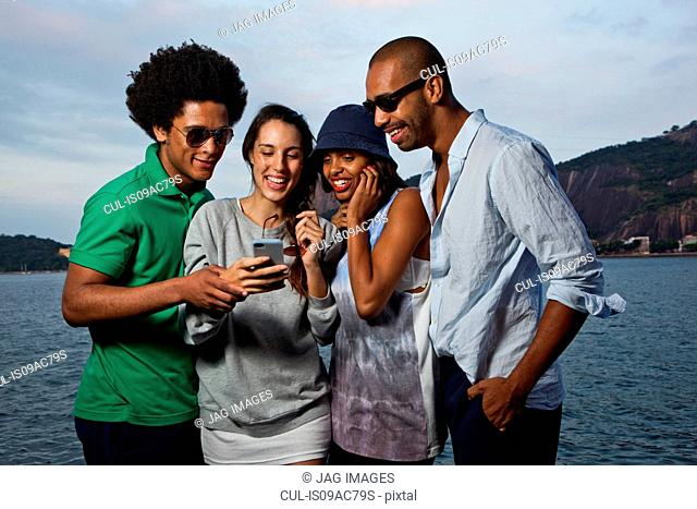 Four friends looking at cell phone