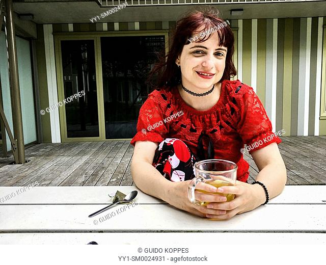 Amsterdam, Netherlands. Portrait of an young, American and redheaded woman, sitting inside her enclosed, apartment garden