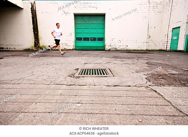 Man running on sidewalk in downtown Vancouver, British Columbia, Canada