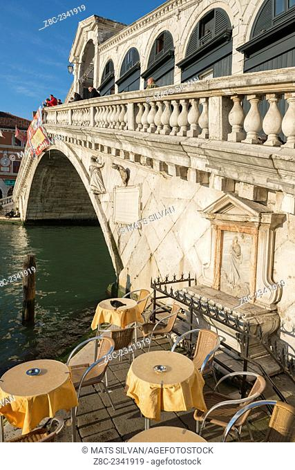 Rialto bridge over Grand canal and Chairs with tables in a sunny day in Venice, Italy