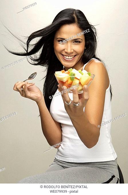 Latin model eating fruit plate