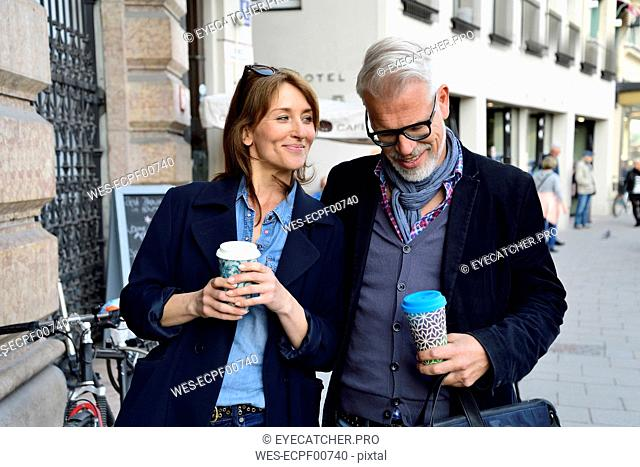 Smiling mature couple with reusable bamboo cups in the city