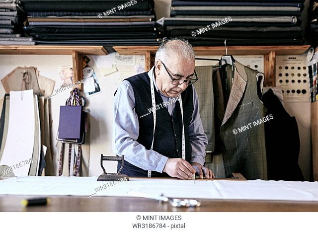 Tailor with measuring tape around neck working with material at bench