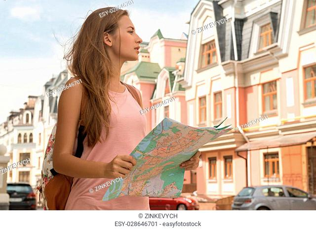 Waist-up portrait of pretty female traveler on the street holding a map in her hands and concentrated looking aside, concept of summer holidays and tourism