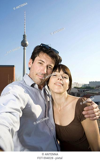 A couple photographing themselves on a rooftop terrace