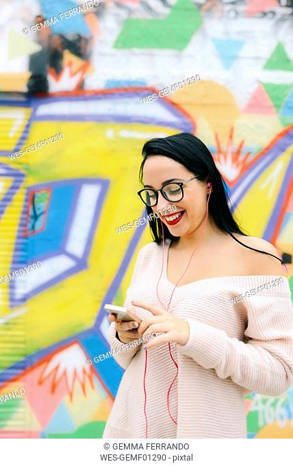 Portrait of happy young woman with earphones and cell phone in front of graffiti wall