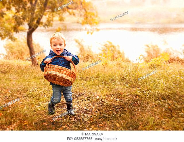 Little boy with basket in autumn forest. Copyspace