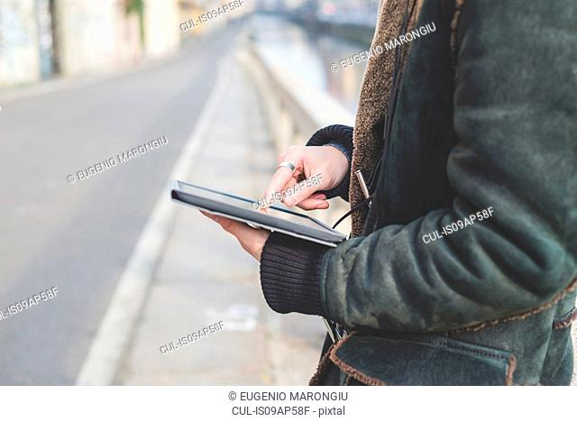 Man using digital tablet by canal, Milan, Italy