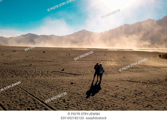 Cinematic shot aerial drone view of tourists walking in a volcanic dusty desert near beautiful Mount Bromo in East Java, Indonesia