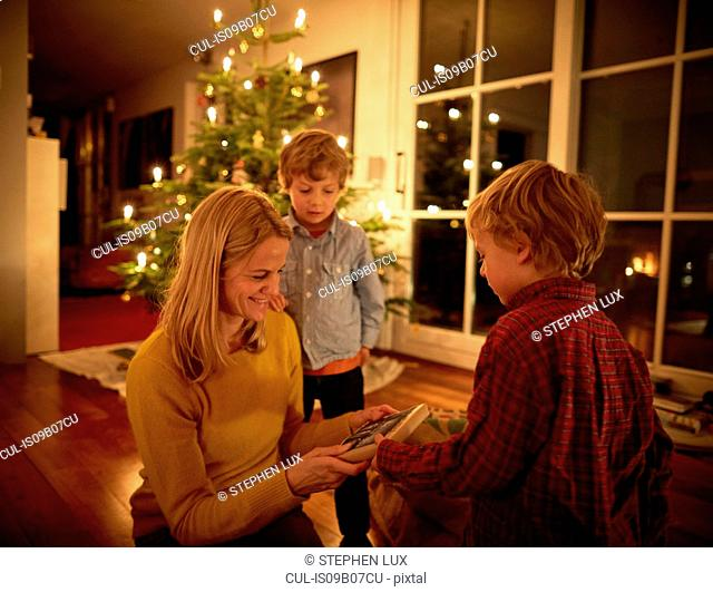 Mother and sons sitting at home at Christmas, exchanging gifts