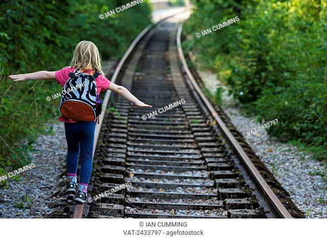 Girl walking along abandoned railway track, near Clecy; Normandy, France