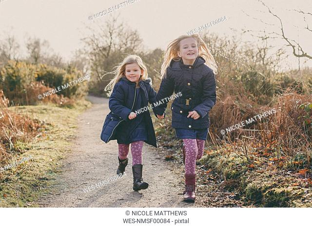 Two sisters running on a rural path together