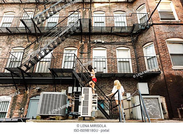Women climbing fire escape ladder of apartment building, Boston, MA, USA